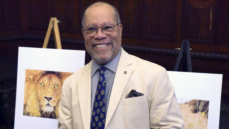 Children's book illustrator Jerry Pinkney poses in front of two of his illustrations Tuesday,...