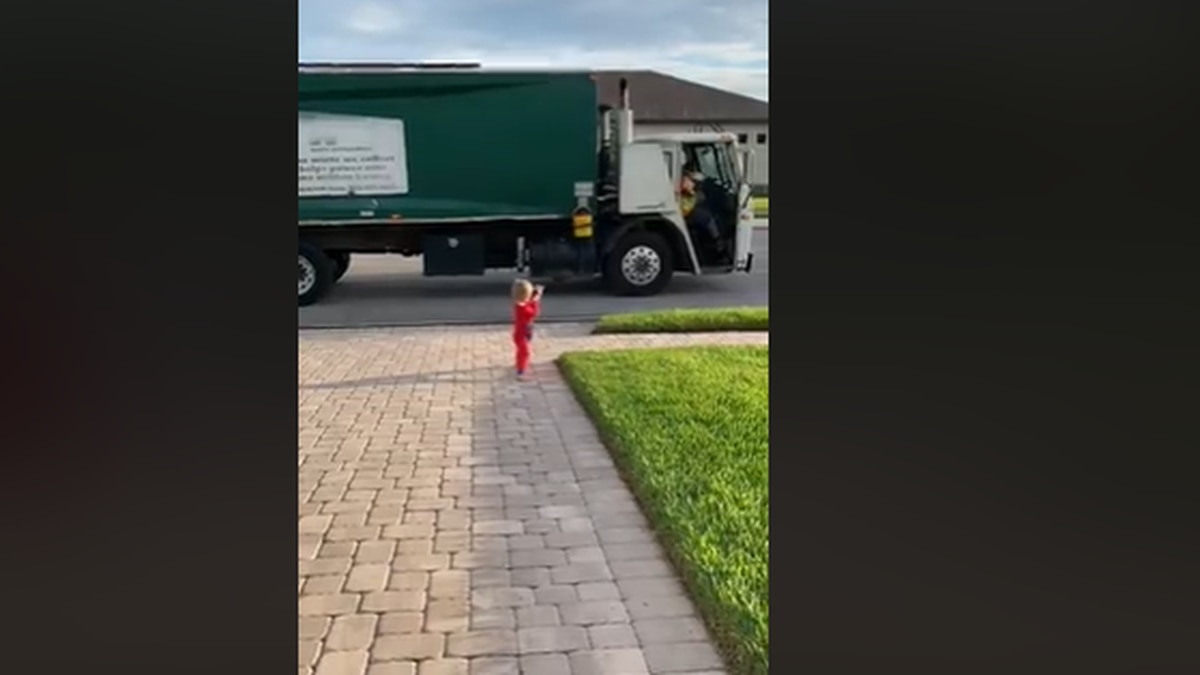 Juan Carceres films his son interacting with local sanitation workers.