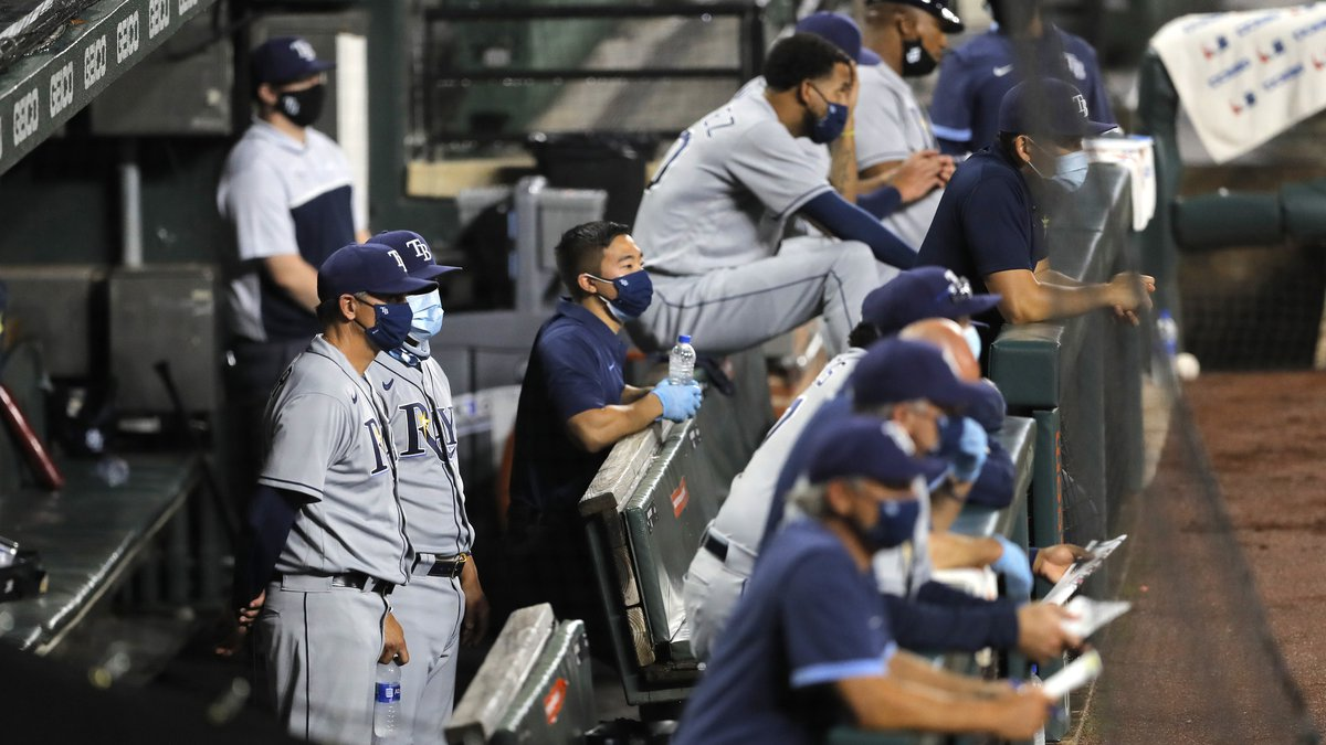 Members of the Tampa Bay Rays wear face masks while standing in the dugout during the second...