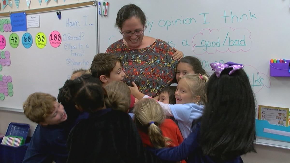 Mrs. Conley's students give her big hug for winning November's Chalkboard Champion award for...