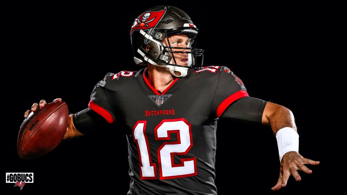 Tom Brady pretends to throw the football while wearing a Tampa Bay Buccaneers uniform for the...